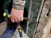 Repair - tool chisel in the hands of the builder. Or finisher stock photo
