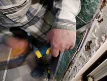 Repair - tool chisel in the hands of the builder. Or finisher royalty free stock photography