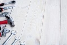 Repair tools on a white wooden background. Jack keys and hammer. Space for text stock photography