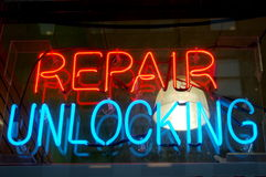 Repair Unlocking Sign. A neon sign in a computer store window advertises repair and emergency unlocking Stock Photo