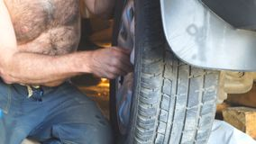 Repair wheels in the garage. Man replaces the wheel stock footage