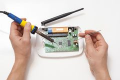 Repair of wi-fi router. Dismantled wi-fi router and tools on a white table Stock Photo