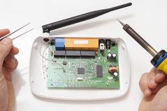 Repair of wi-fi router. Dismantled wi-fi router and tools on a white table Stock Photography