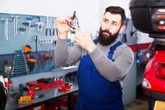 Repair wizard displays the motorcycle spare. Hard-working repair wizard displays the motorcycle spare in the workplace Royalty Free Stock Photography