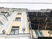 Repair work on the facade of the building with the help of wooden scaffolding, structures, restoration of the old house stock photo