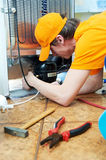 Repair work on fridge appliance. Repairman makes refrigerator appliance troubleshooting and maintenance works Royalty Free Stock Photography