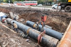 Repair work of heating duct. The workers, welders made by electric welding on large iron pipes at a depth of excavated trench. Samara, Russia - October 1, 2017 stock photo