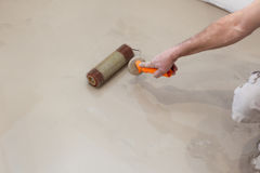 Repair work. Pouring floors in the room. Fill screed floor repair and furnish. Worker align cement with roller Stock Images