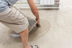 Repair work. Pouring floors in the room. Fill screed floor repair and furnish. Worker pouring concrete on the floor Stock Photos