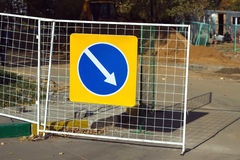 Repair work. Road sign indicating detour hanging on fence Stock Image