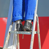 Repair. The worker's feet in a uniform on a step-ladder. Royalty Free Stock Photos
