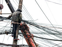 Repair workers are swinging on cable posts to fix the line of in. Repair workers are swinging on cable posts to fix the line of network cable and wire on Royalty Free Stock Photo