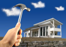 Repair works. Hand holding hammer. Big modern house on the background Royalty Free Stock Images