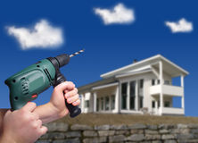 Repair works. Hands holding drill. Big modern house on the background Stock Photo