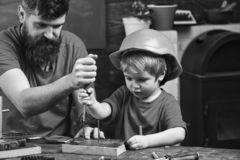 Repair and workshop concept. Boy, child busy in protective helmet learning to use screwdriver with dad. Father, parent stock photography