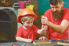Repair and workshop concept. Boy, child busy in protective helmet learning to use screwdriver with dad. Father, parent. With beard teaching little son to use stock photography