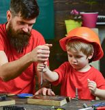 Repair and workshop concept. Father, parent with beard teaching little son to use tool screwdriver. Boy, child busy in. Protective helmet learning to use royalty free stock photos