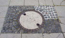 Repaired man hole cover on the square. Stock Photos
