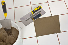 Repaired old white tiles floor with Trowel Stock Image