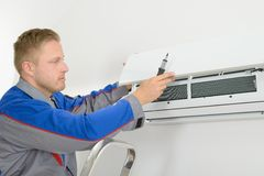 Repairer repairing air conditioner. Young Man Repairing Air Conditioner Standing On Stepladder Stock Images