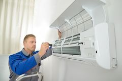 Repairer repairing air conditioner Stock Images