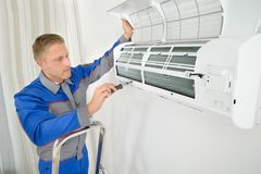 Repairer repairing air conditioner. Young Man Repairing Air Conditioner Standing On Stepladder Royalty Free Stock Images