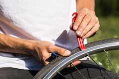 Repairing bicycle wheel outdoors during trip. Close up image of persons hands using tire levers to replace inner tube of bicycle wheel royalty free stock image