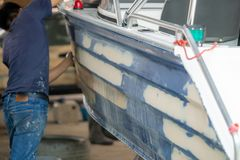 Aluminum boat painting procedure at service center. Repairing boat body by puttying close up work after the accident by working sanding primer before painting royalty free stock image