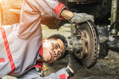 Repairing the brake of the car. Technicians in grey uniform are repairing the brake of the car, Automotive industry and garage concepts stock photo