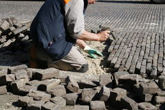 Repairing the brick road. Man with chisel on his knees repairing the brick road Royalty Free Stock Photography