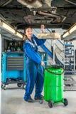 Repairing Car On för kvinnlig mekaniker hydraulisk elevator i garage fotografering för bildbyråer