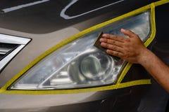 Repairing car headlight, worker hand sanding plastic stock photo