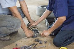 Repairing a car suspension. fixing a car shock absorber in auto. Mechanic shop royalty free stock photography