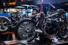 Repairing custom bike. Young technician standing by custom bike during work stock photos