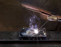 Repairing a defect hard disk. With welding apparatus. Protective shield and smoke on rusty background Stock Photos