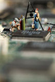 Repairing Electronic Circuitry. A miniature model figurine of a welder at work on a circuit board, macro Royalty Free Stock Photos