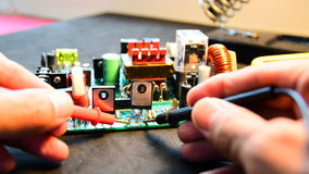 Repairing electronics board. Technician are measuring the power of electronic devices on board by digital meter stock video