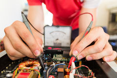 REPAIRING ELECTRONICS WITH TEST EQUIPMENT. IN SERVICE CENTER BY ENGINEER Royalty Free Stock Photography