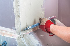 Repairing fireplace surface with spackle and trowel by hand Stock Photo
