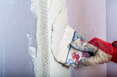 Repairing fireplace surface with spackle and trowel by hand Royalty Free Stock Images