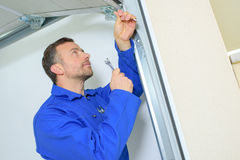 Repairing garage door hinge Stock Photo