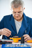 Repairing hair dryer. Senior adult Electrician checking and repairing old hair dryer royalty free stock photography