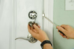 Repairing installing door deadbolt lock on house closeup. Closeup of a professional locksmith is installing or repairing a new deadbolt lock on a house exterior Royalty Free Stock Images