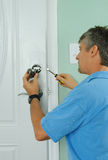 Repairing installing door deadbolt lock on house. A professional locksmith is installing or repairing a new deadbolt lock on a house exterior door with the Royalty Free Stock Photos