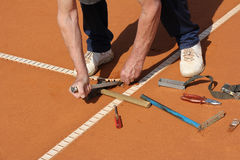 Repairing lines on a tennis court Stock Image