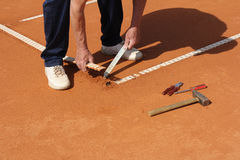 Repairing lines on a tennis court Stock Photo