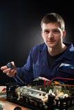 Repairing man in blue robe Stock Image