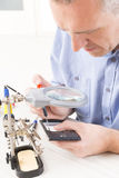 Repairing mobile phone in the electronic workshop Stock Photos