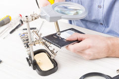 Repairing mobile phone in the electronic workshop Royalty Free Stock Photo