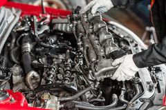 Repairing of modern diesel engine, workers hands and tool. Car mechanic looking at engine for analysis symptoms of car. At maintenance repair service station stock image